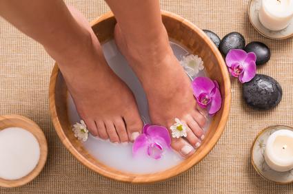 Füße stehen im Wasser, welches mit Orchideen verfeinert wurde um anschließend die Hornhaut elektrisch zu entfernen.